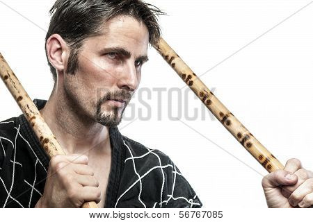 Martial arts master with black combat dress and two short bamboo sticks isolated on white background poster