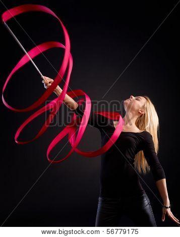 Artistic photo of young rhytmic gymnast using ribbon.