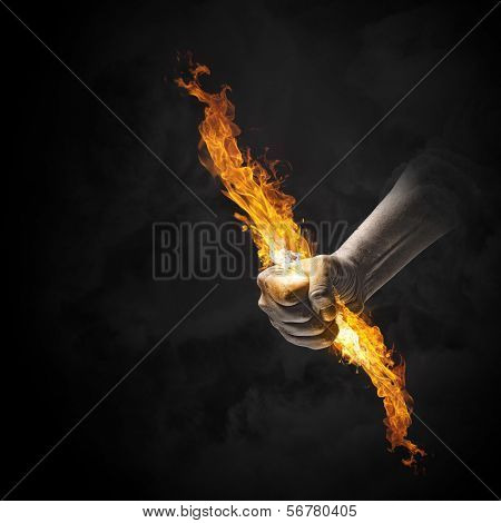 Close up of human hand holding fire flame
