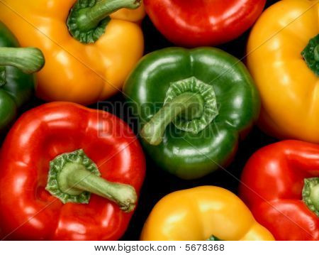 Red, Green And Yellow Bell Peppers On Black Background