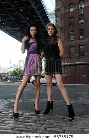 Two models posing under Manhattan bridge