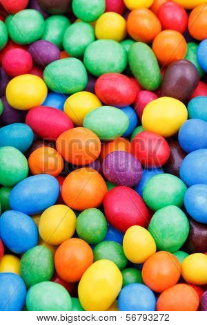 background from many multi-colored chocolate candy dragees close up poster