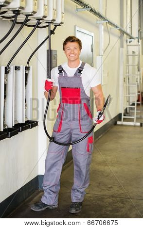 Cheerful serviceman holding hose with unbottled motor oil in a car workshop