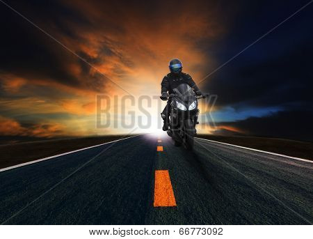 young man riding motorcycle on curve of asphalt country road against dusky sky