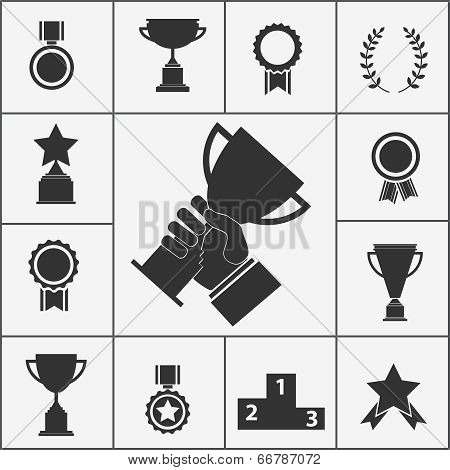 Set of black silhouette vector trophy and award icons with cups  ribbons  rosettes  stars  podium  medals  medallions and a hand holding aloft a large trophy in the centre in celebration of a victory poster