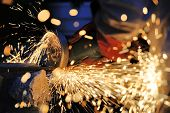 Worker cutting metal with grinder. Sparks while grinding iron poster