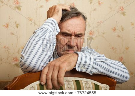 Elderly man grieves at home.
