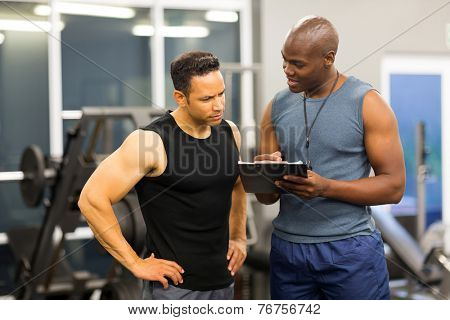 african personal trainer helping man to fill the membership form of health club