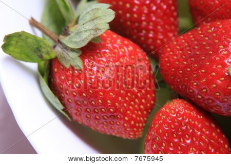Red strawberries with green leaves in a white bowl