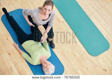 Female Trainer Helping Senior Woman Do Leg Stretches At Rehab