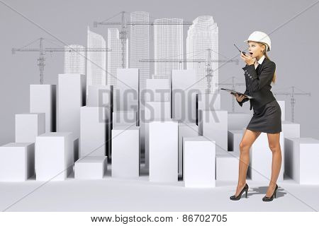 Business woman using walkie-talkie. Many white cubes with wire-frame buildings