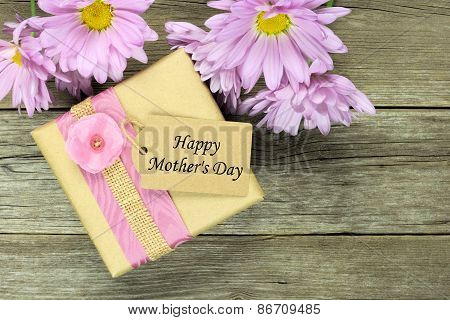 Mother's Day gift box on wood with daisies
