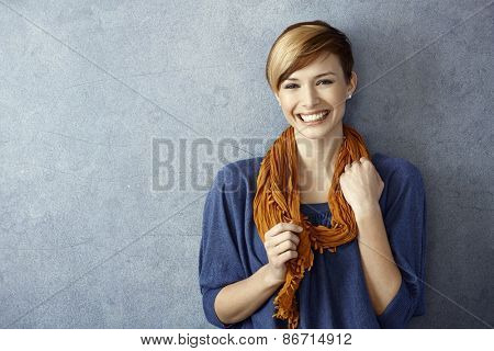 Portrait of young woman smiling happily standing by wall. Copy space.