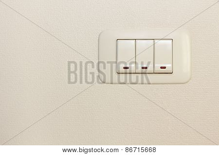 Threefold Multiply Light Switch On White Wall.