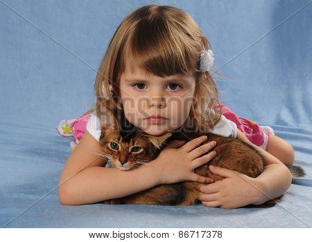 Little Girl Lying With Somali Kitten Ruddy Color