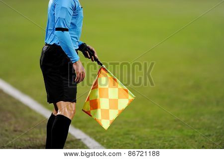Assistant referees signalling with the flag on the sideline during a soccer match poster
