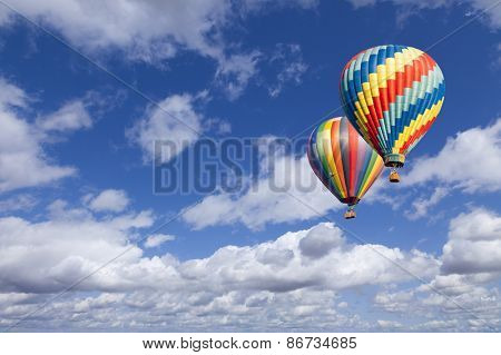 Two Hot Air Balloons Up In The Beautiful Blue Sky.