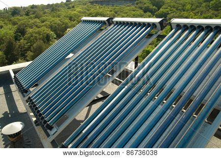 Vacuum solar water heating system on the house roof. poster