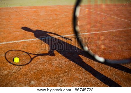 Shadow of a tennis player in action on a tennis court (conceptual image with a tennis ball lying on the court and the shadow of the player positioned in a way he seems to be playing it) poster