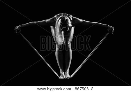 Sportswoman exercising with a resistance band on black background.