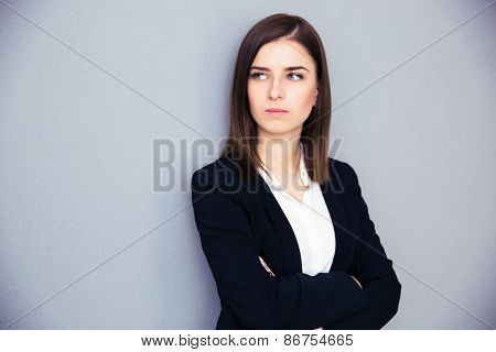 Young serious businesswoman with arms folded standing over gray background. Looking away