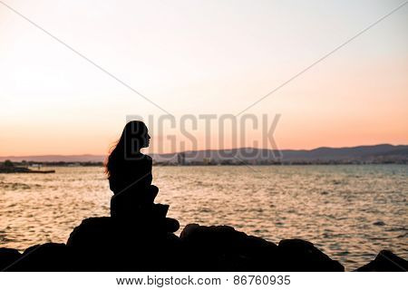 Girl Sittinng On The Stones On Evening Sunset