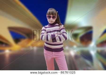 Teenage girl in pink wears sunglasses with modern city in background