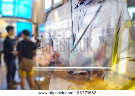 Double Exposure Manipulation Of Business Man Using Tablet And Blur Background Of Theatre E-ticket Sy