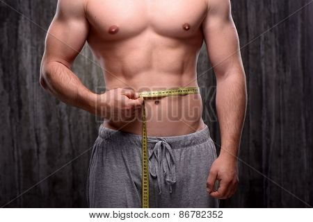 Close up photo of young well formed sporty man measuring his waist with yellow tape. Fitness concept poster