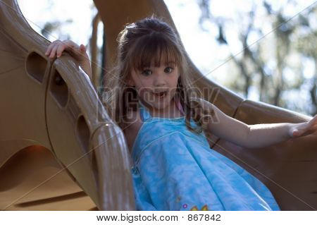 Young Girl On Slide At Playground
