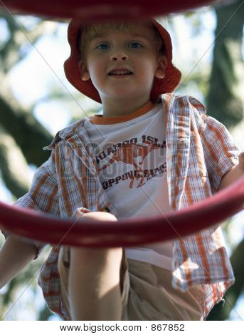 Young Boy Climbing On Playground Equipment