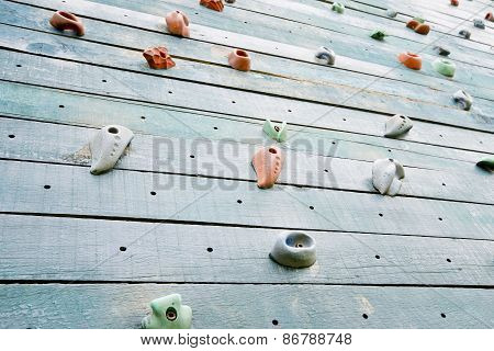 Grunge Surface Of An Artificial Rock Climbing Wall With Toe And Hand Hold Studs.