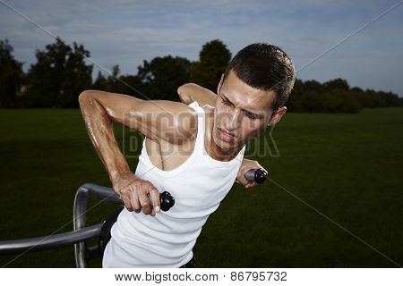 Very slim and tall man exercising on outdoor location on public park fitness in summer time. poster