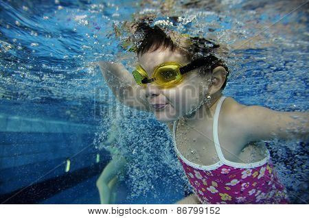 Funny Happy Toddler Girl Swimming Underwater In A Pool With Lots Of Air Bubbles