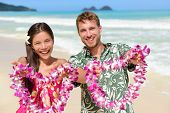 Welcome to Hawaii - Hawaiian people showing leis flower necklaces as a welcoming gesture for tourism. Travel holidays concept. Asian woman and Caucasian man on white sand beach in Aloha clothing. poster