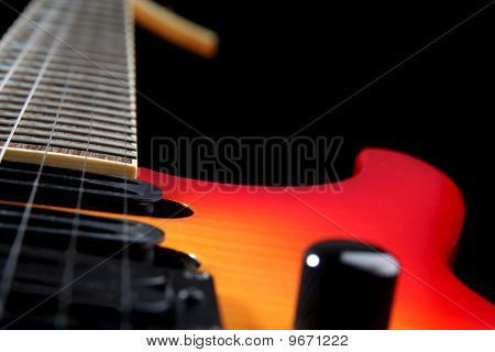 A six string electric guitar isolated on a black background