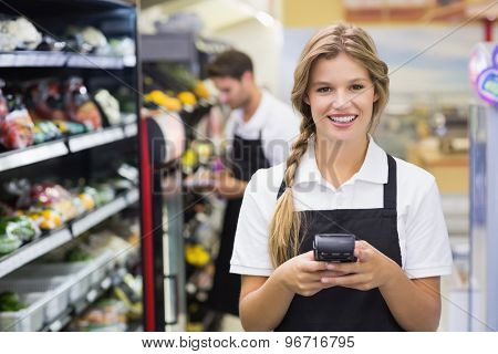 Portrait of smiling pretty blonde woman using handheld at supermarket