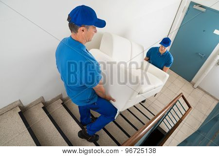 Two Movers Carrying Sofa On Staircase