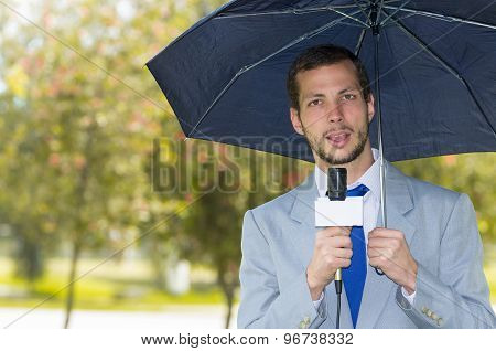 Successful handsome male journalist wearing light grey suit working in rainy weather outdoors park e