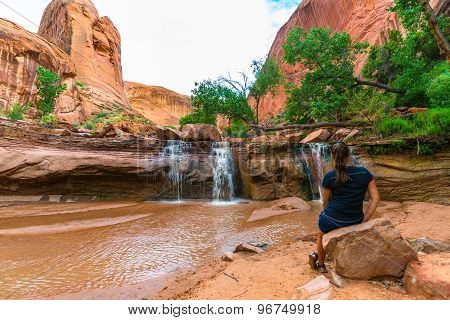 Girl Sitting In Front Of Waterfall