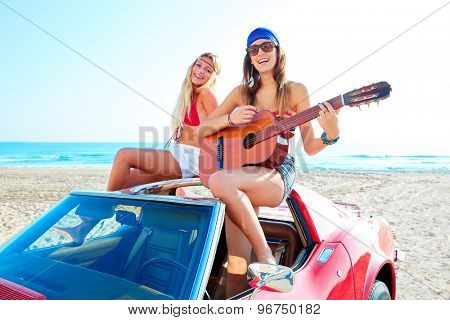 girls having fun playing guitar on th beach with a convertible car poster