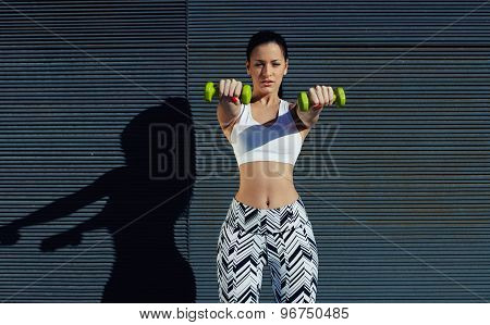 Sporty woman holding weights with hands up at her front getting arms in great shape