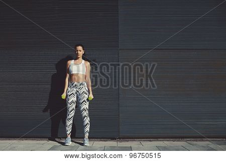 Female look to you while taking break during her training outdoors against black background