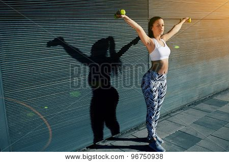 Sporty young woman lifting weights standing with arms outstretched against black wall background