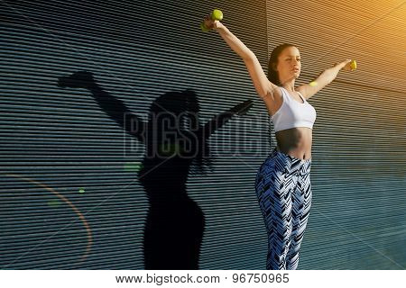 Athletic female with perfect figure getting her arms in great shape while lifting weights at outdoor