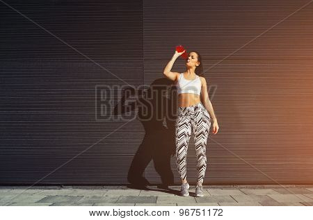 Young fit woman with beautiful figure refreshing with energy drink against black wall in the city