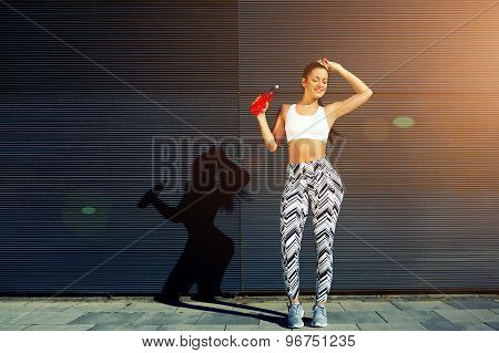 Female runner hold energy drink bottle while resting after fitness training outdoors in the city