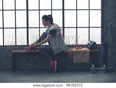 Sporty Woman In Profile Sitting On Bench Tying Shoe In Loft Gym
