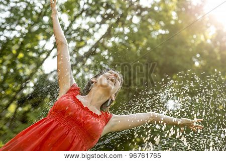 Happy Young  Woman Standing Under A Spray Of Water On A Hot Summer Day With Her Arms Outstretched Re