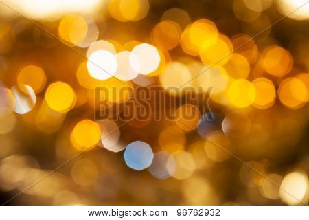 abstract blurred background - yellow and brown shimmering Christmas lights of electric garlands on Xmas tree poster